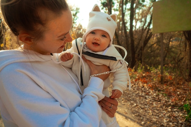 Beautiful young mom with baby girl in autumn