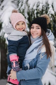 Красивая молодая мама с милой дочерью в зимнем парке
