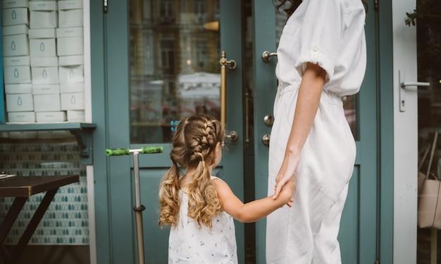 Красивая молодая мать и милая маленькая дочь гуляют по улице