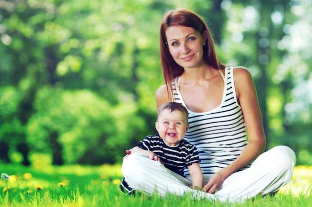 緑の芝生の上の公園に座っている美しい若い母と娘