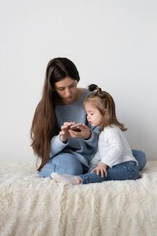 美しい若い母親と彼女の小さな娘は、自宅のベッドに座っています。手に携帯電話のスマートフォン。女性は働き、女の子は彼女を悩ませます。テキストの場所