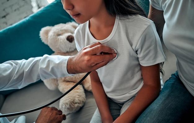 아름 다운 젊은 어머니와 집에서 그녀의 작은 딸. 의사가 청진기를 사용하여 작은 환자를 검사하고 있다