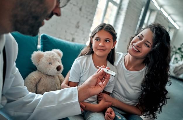 아름 다운 젊은 어머니와 집에서 그녀의 작은 딸. 의사가 온도계를 사용하여 작은 환자를 검사하고 있습니다.