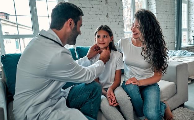 아름 다운 젊은 어머니와 집에서 그녀의 작은 딸. 의사가 작은 환자를 검사하고 있습니다.
