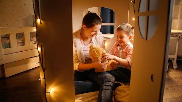 Красивая молодая мать и маленький сын, играя с плюшевым мишкой ночью перед сном. понятие о детской игре и семье, проводящей время вместе в ночное время.