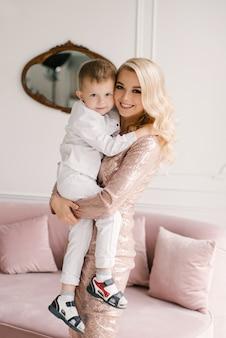 美しい若い母と息子が寄り添い、自宅でスマートな服で遊ぶ