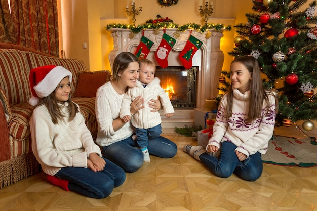 Beautiful young mother, baby son and two daughters on floor next to fireplace on christmas