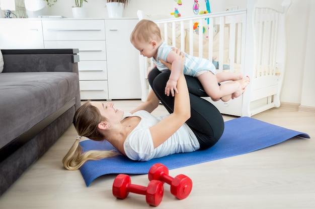 그녀의 아기와 함께 바닥에 운동 아름 다운 젊은 어머니