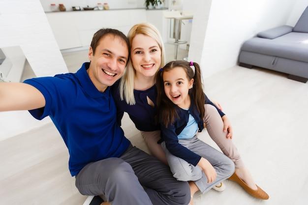 Красивая молодая мать, отец и их дочь делают селфи по телефону и улыбаются, сидя дома