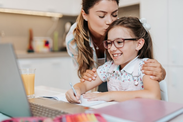 Красивая молодая мать, помогая своей младшей дочери с домашним заданием.