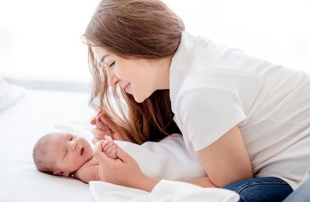 아름 다운 젊은 어머니는 침대에서 잠자는 신생아 딸의 손을 잡고 미소로 그녀를 바라보고 있습니다. 부모와 유아. 출산의 가족 순간