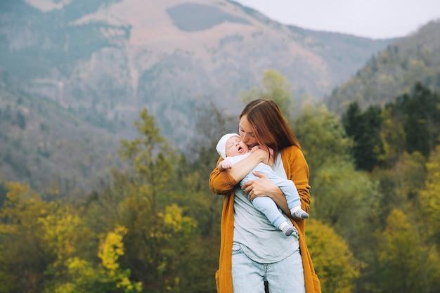 Красивая молодая мать держит на руках своего ребенка на фоне гор