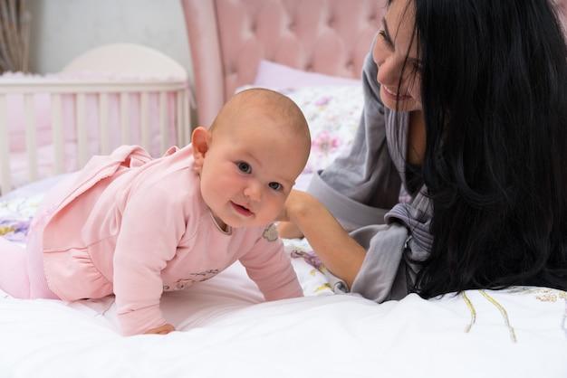 一緒に時間を楽しんで、笑顔のベッドでピンクのドレスを着た彼女のかわいい幸せな女の赤ちゃんと一緒に横たわっているバスローブの美しい若い母親