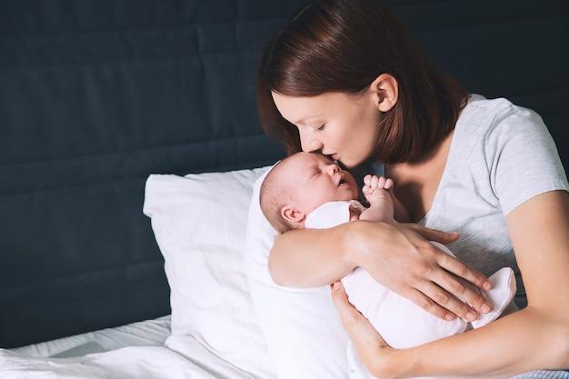 Красивая молодая мать целует своего новорожденного ребенка спящий ребенок в руках любящей матери