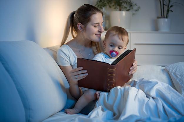 寝る前に赤ちゃんに本を読んでいる美しい若い母親
