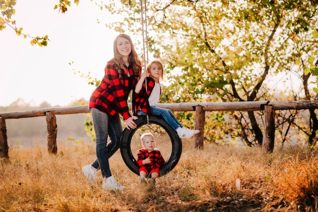 美しい若い母親がロープでタイヤに息子と娘を乗せます