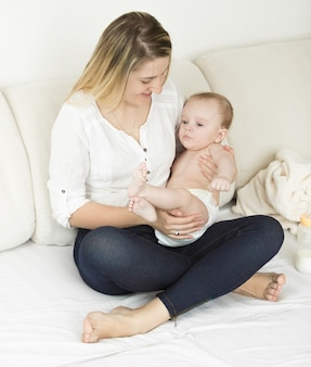그녀의 귀여운 아기와 함께 침대에 앉아 아름 다운 젊은 어머니 프리미엄 사진