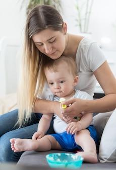ソファに座ってお粥で赤ちゃんを養う美しい若い母親