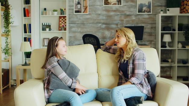 아름 다운 젊은 어머니는 그녀의 딸과 대화를 나누는 거실에서 소파에 앉아.