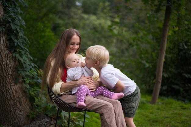 自然に2人の子供と座っている美しい若い母親。子供との休暇。幸せな家族の概念