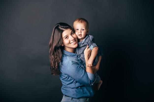 아름 다운 젊은 어머니 서 어두운 배경 앞에서 그녀의 팔에 그녀의 아기를 들고, 귀여운 아이와 검은 머리를 가진 아가씨