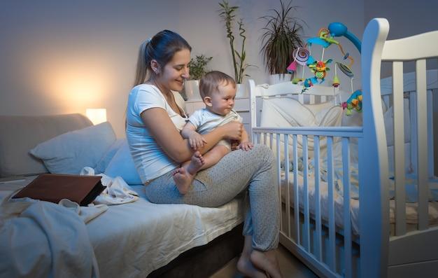 Красивая молодая мать, вынимающая ребенка из кроватки ночью