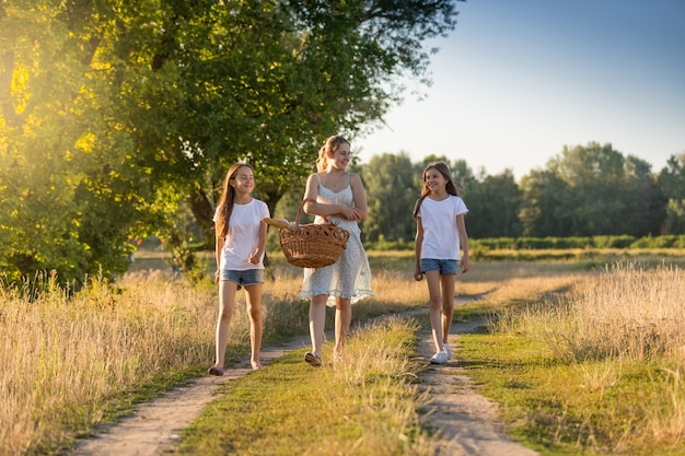 Beautiful young mother walking to picnic with her two daughter