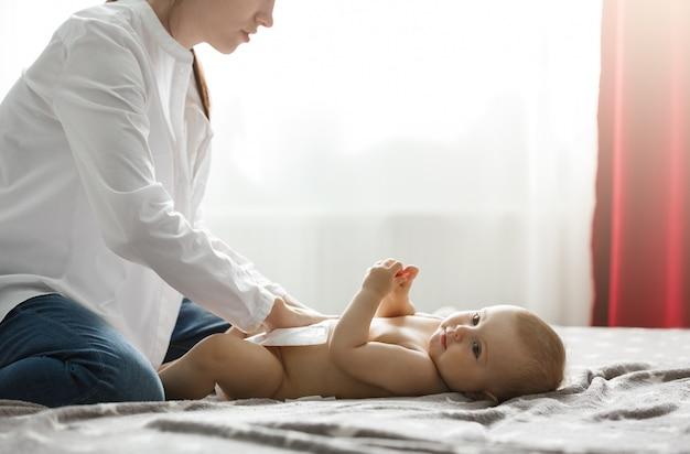 Bella giovane madre in camicia bianca e jeans che mettono il pannolino sul neonato sveglio che prepara per la cena in famiglia con i nonni. trascorrere del tempo speciale con la famiglia.