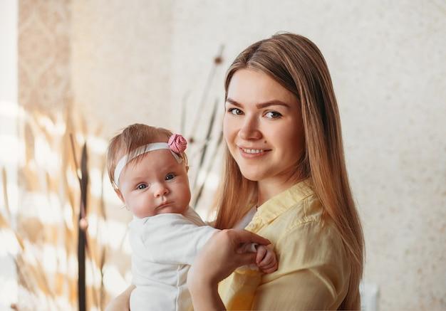 彼女の腕の中で女の赤ちゃんを持つ美しい若い母親。カメラを見てください