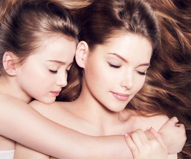 目を閉じて一緒に横たわっている8歳の小さな娘を持つ美しい若い母親