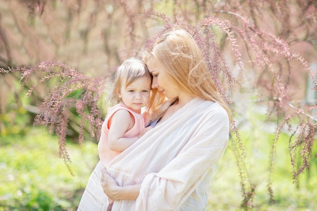 Beautiful young mother with baby girl in her arms. concept of happy family, motherhood. mother playing with her child in blooming garden in spring