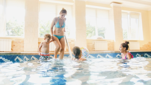 Beautiful young mother with children walking on staircase in swimming pool