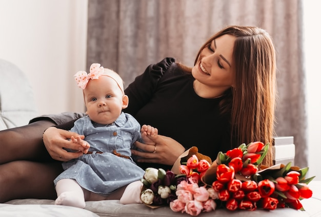 Beautiful young mother with daughter baby on the bed with flowers. congratulations on mother's day