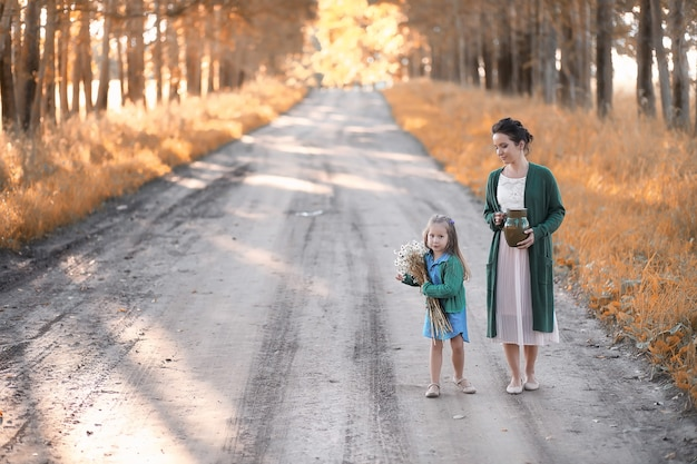 Красивая молодая мать с дочерью, идущей по дороге