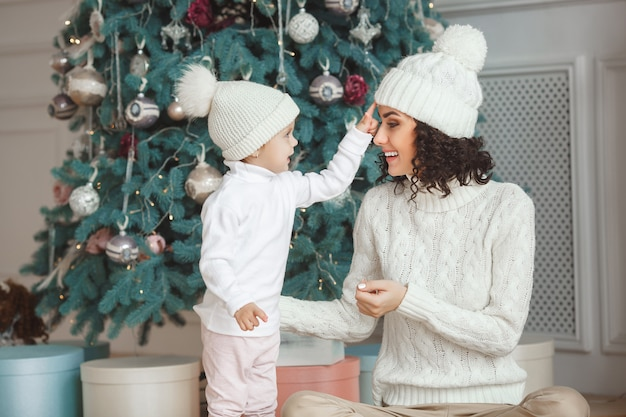 Beautiful young mother with her cute little daughter celebrating christmas holidays. happy family opening xmas presents
