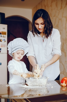 A beautiful young mother with her little daughter is cooking in the kitchen at home