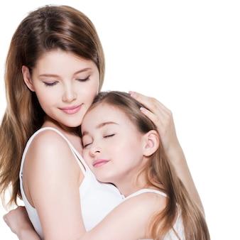 Bella giovane madre con una piccola figlia di 8 anni si abbracciano in studio