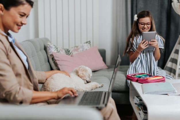 Красивая молодая мать работает из дома, пока ее дочь смотрит онлайн-класс школы. социальное дистанцирование и образ жизни, связанный с covid-19 или коронавирусом.