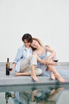 수영장에서 시간을 보내고 좋은 와인을 마시는 사랑에 아름다운 젊은 다민족 부부