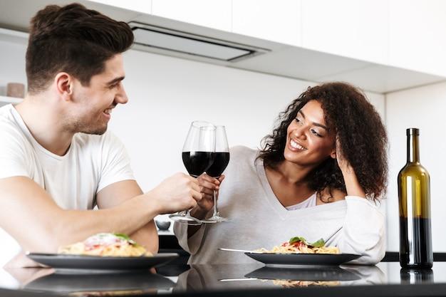 家でロマンチックな夕食を食べ、赤ワインを飲み、パスタを食べ、乾杯する美しい若い多民族のカップル