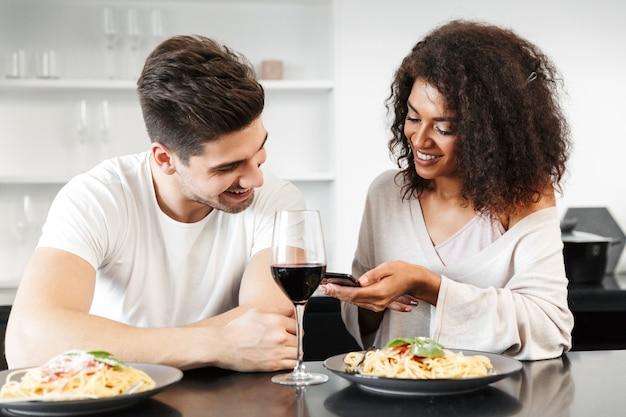 Красивая молодая многонациональная пара, романтический ужин дома, пить красное вино и есть макароны, используя мобильный телефон