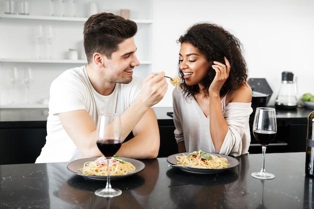 家でロマンチックな夕食を食べ、赤ワインを飲み、パスタを食べる美しい若い多民族のカップル
