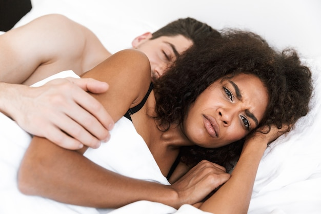 Beautiful young multiethnic couple relaxing in bed under blanket, woman frowning