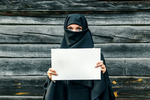 A beautiful, young, muslim girl in a black veil with a closed face against a gray tree. in  handsa sheet of paper. copyspace.