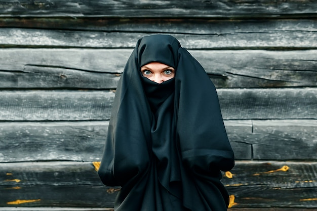 A beautiful, young, muslim girl in a black veil with a closed face on a gray tree  holds her hands behind her head. copyspace.