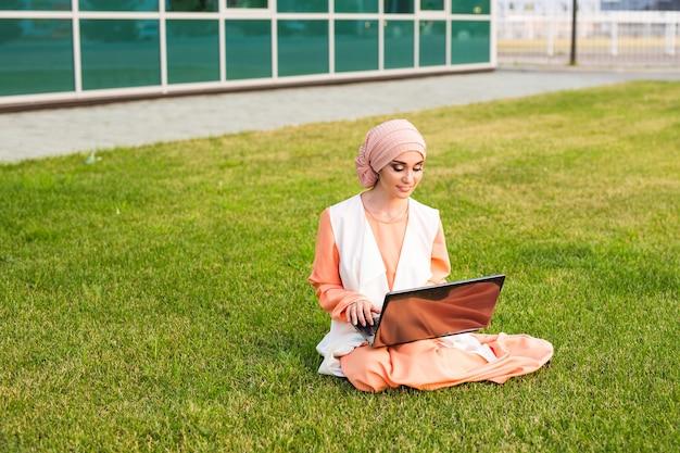 ノートブックと一緒に座っている美しい若いイスラム教徒の少女
