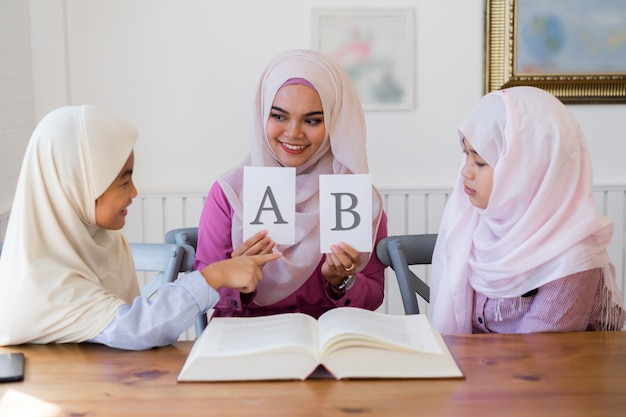 Beautiful young muslim teacher holding two white sheets and cute asian muslim girls in classroom.