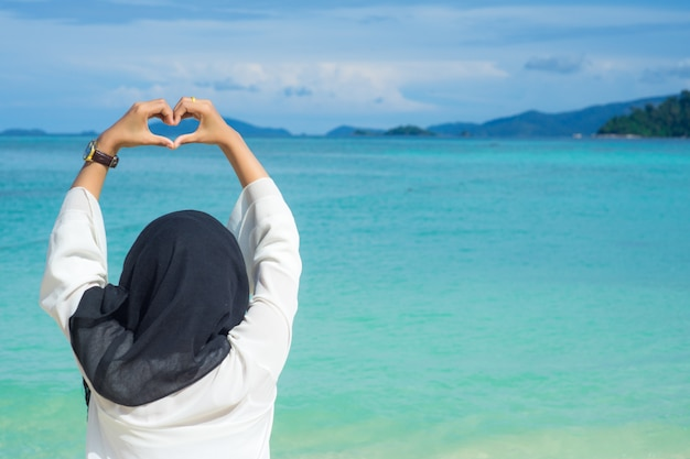 Beautiful young muslim woman black hijab lift hand showing heart shape at lipe thailand island with the turquoise ocean water