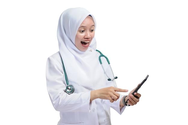 白い背景で隔離のスマートフォンを指している美しい若いイスラム教徒の女性の看護師または医師