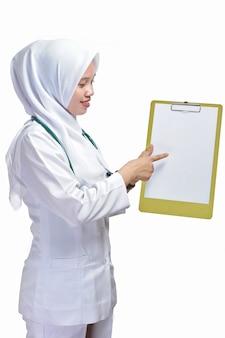 白い背景で隔離クリップボードに白紙を指す美しい若いイスラム教徒の女性看護師または医師